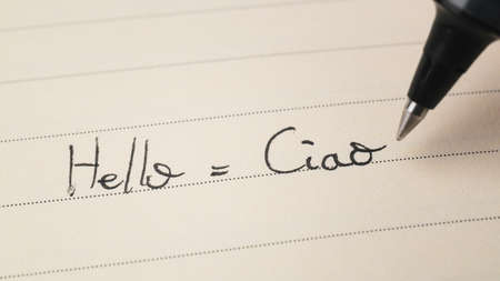 Beginner Italian language learner writing Hello word Ciao for homework on a notebook macro shot