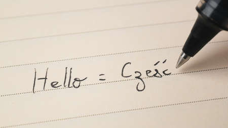 Beginner Polish language learner writing Hello word Czesc for homework on a notebook macro shot