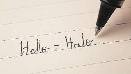 Beginner Indonesian language learner writing Hello word Halo for homework on a notebook macro shot