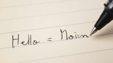 Beginner Luxembourgish language learner writing Hello informal word Moien for homework on a notebook macro shot 免版税图像