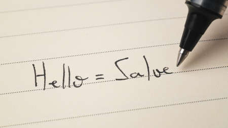 Beginner Italian language learner writing Hello formal word Salve for homework on a notebook macro shot