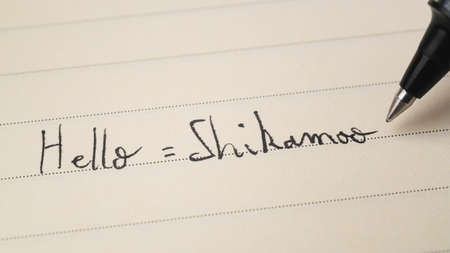 Beginner Swahili language learner writing Hello formal word Shikamoo for homework on a notebook macro shot
