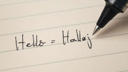 Beginner Danish language learner writing Hello word Halloj for homework on a notebook macro shot