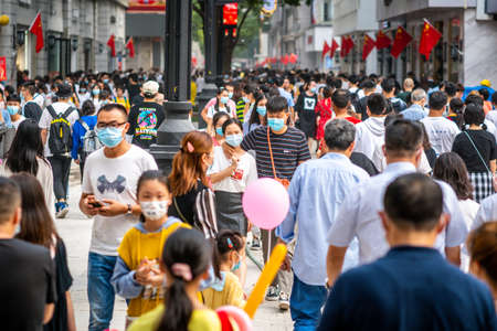Wuhan China, October 1, 2020: Crowd of people wearing surgical face mask on the 2020 China national day and first day of golden week holidays in Jianghan pedestrian road in Wuhan Hubei China