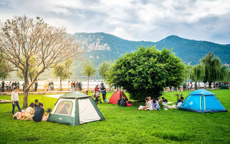 Kunming China, October 3, 2020: Chinese people enjoying holidays in Dianchi Haigeng park with tents on the grass and lake and western hills in background in Kunming Yunnan China 新闻类图片
