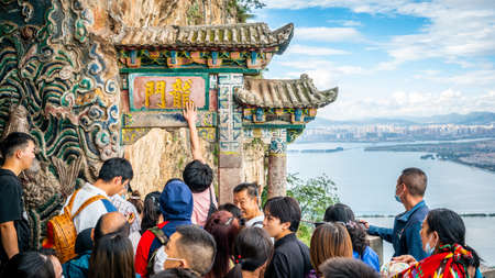Kunming China, 3 October 2020: Chinese tourists trying to touch the West Hill dragon gate or Longmen for good luck in Kunming Yunnan China 新闻类图片