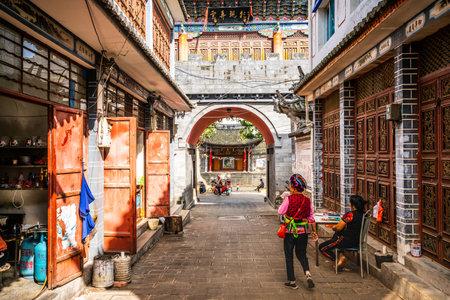 Dali China, 6 October 2020: Zhoucheng ancient village alley view with Bai minority woman in traditional dress in Zhoucheng Dali Yunnan China
