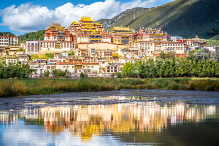 Ganden Sumtseling monastery with beautiful water reflection on lake in Shangri-La Yunnan China