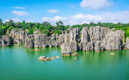 Limestone rock formation over beautiful lake and blue sky at Shilin stone forest park in Yunnan China