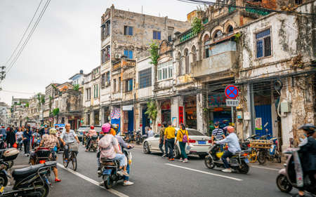 Haikou China, 21 March 2021: Street view of Haikou old town with ancient decrepit buildings and crowded Boai north road with people and scooters in Qilou Haikou Hainan China