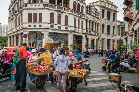 Haikou China, March 21, 2021: Tourists buying fruits at street food stall in Water-alley street with old colonial buildings and people in Haikou old town Hainan China