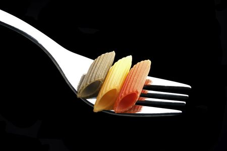italian penne pasta on a fork on black background photo