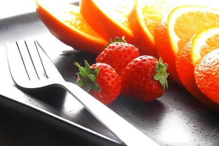 orange and strawberries on a plate on white background