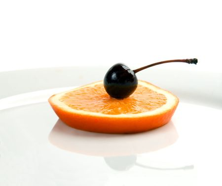 slice of orange with cherry on top isolated on a plate with reflection Stock Photo - 2757842