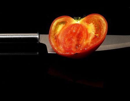 tomato sliced with knife on black background photo