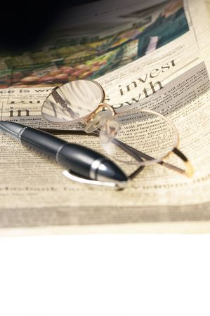 opthalmology: pen and glassesand newspaper over white glass table