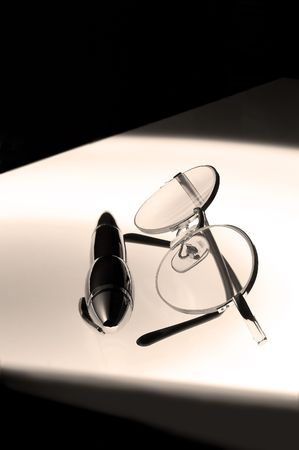 opthalmology: pen and glasses over white glass table