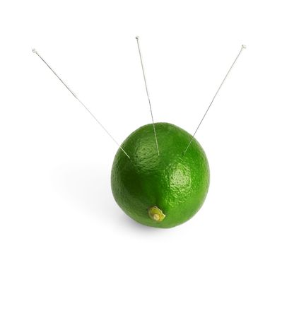 lime with acupuncture needles isolated on white background photo