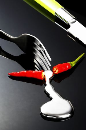 red chili pepper melting a fork while be cutted on a black stone Stock Photo - 3707217