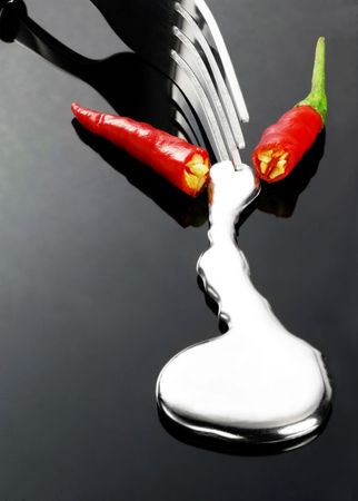 red chili pepper melting a fork while be cutted on a black stone