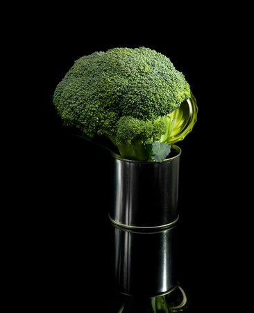 fresh vivid green broccoli on a tin can over black background photo