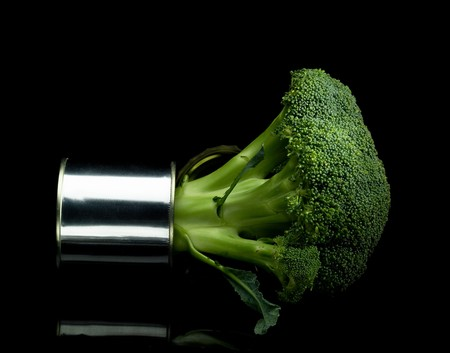 florets: fresh vivid green broccoli on a tin can over black background