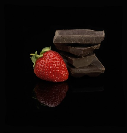 bitter fruit: fresh vivid colored strawberry and broken chocolate bar over black background