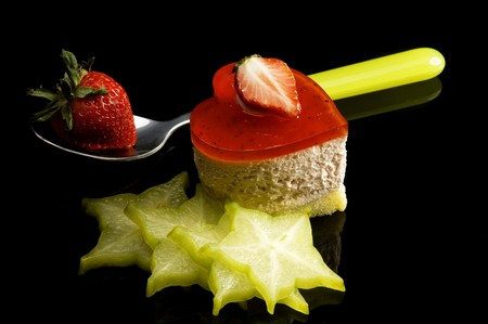 heart shaped strawberry cake with carambola or star fruit decoration over black background Stock Photo - 4029420