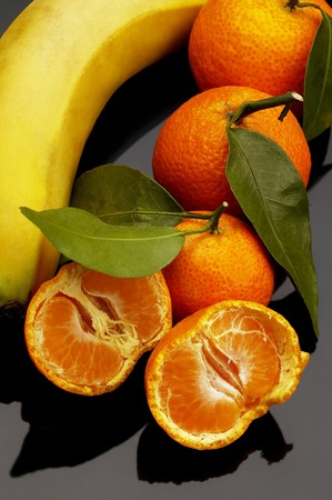 vivid orange tangerine and banana on black reflective surface photo