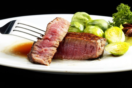 rare: juicy filet mignon on plate with brussel sprout over black background
