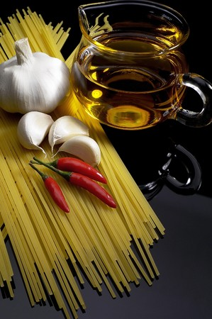 love: pasta garlic olive oil and red chili pepper ove black reflective surface