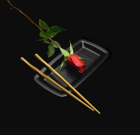 red rose on a japanese plate with chopstick over black background Stock Photo - 4625653