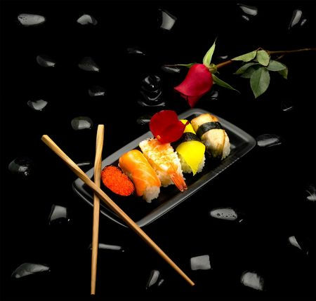sushi plate: assorted sushi plate on black pebbles over black background Stock Photo