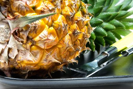 ripe vivid pineapple on a black plate with knife and fork photo