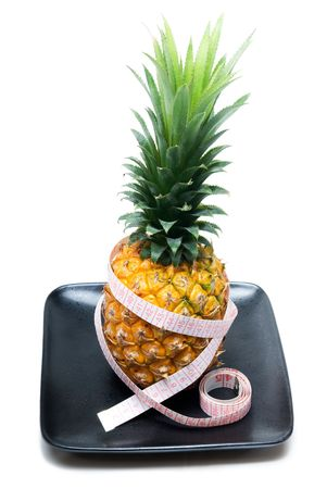ripe vivid pineapple on a black plate with tape meter photo