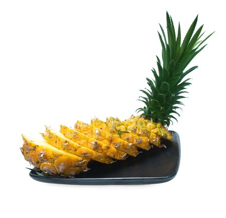 pineapple sliced on a black plate isolated on white background photo
