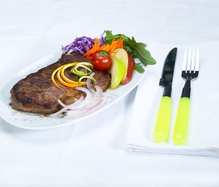 fresh juicy beef ribeye steak grilled with lemon and orange peel on top and vegetables beside