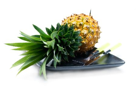 pineapple on a black plate with knife and fork isolated on white background photo