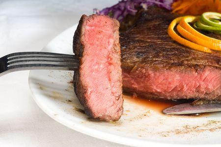 ribeye: fresh juicy beef ribeye steak sliced ,with lemon and orange peel on top  and vegetable beside