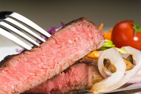 fresh juicy beef ribeye steak sliced ,with lemon and orange peel on top  and vegetable beside photo