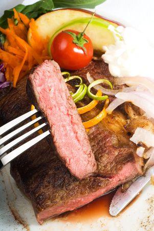 fresh juicy beef ribeye steak sliced ,with lemon and orange peel on top  and vegetable beside