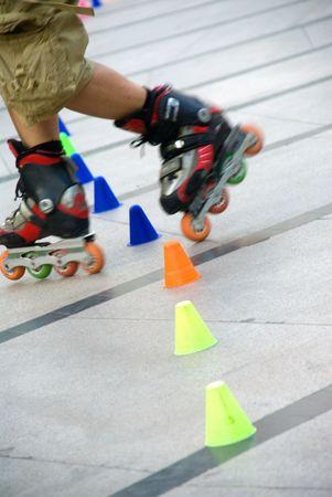 young guy skating slalom around colorfull cones photo