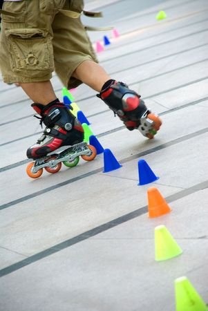 young guy skating slalom around colorfull cones photo