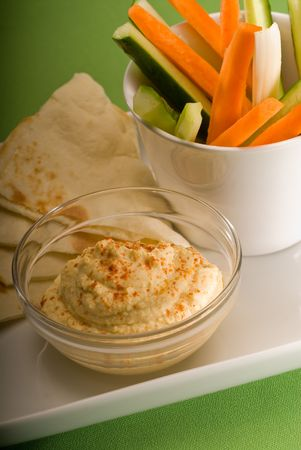 middle eastern hummus dip on a glass bowl with homemade pita brad and raw vegetable