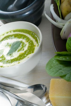 fresh spinach soup on a white bowl with sage and cream on top photo