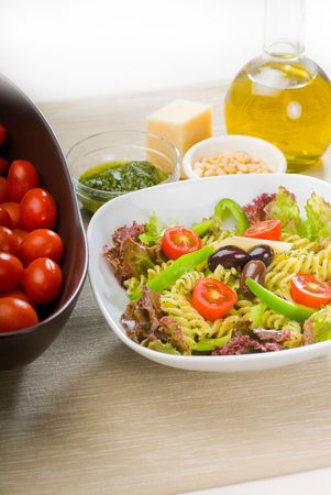fresh healthy homemade italian fusilli pasta salad with parmesan cheese,pachino cherry tomatoes, black olives and mix vegetables ,dressed with extra-virgin olive oil and pesto sauce photo