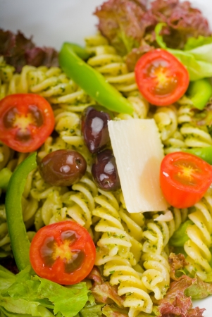 healthy homemade italian fusilli pasta salad with parmesan cheese, pachino cherry tomatoes, black olives and mix vegetables, dressed with extra-virgin olive oil and pesto sauce photo