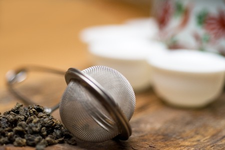 dry green chinese tea set,with strainer closeup,cups and teapot on background over old wood board Stock Photo - 6971668