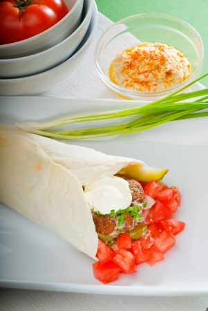 fresh traditional falafel wrap on pita bread with fresh chopped tomatoes photo