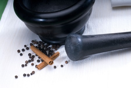 pestel: black stone mortar and pestel with cinnamon and pepper